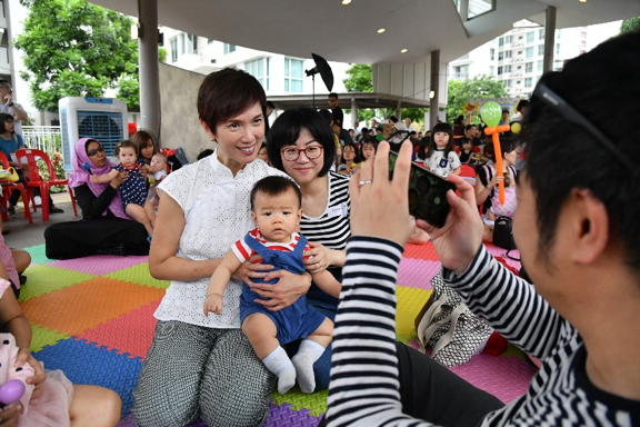Minister Josephine Teo posing for a photo with a participating family at the Embracing PArenthood Celebrations.