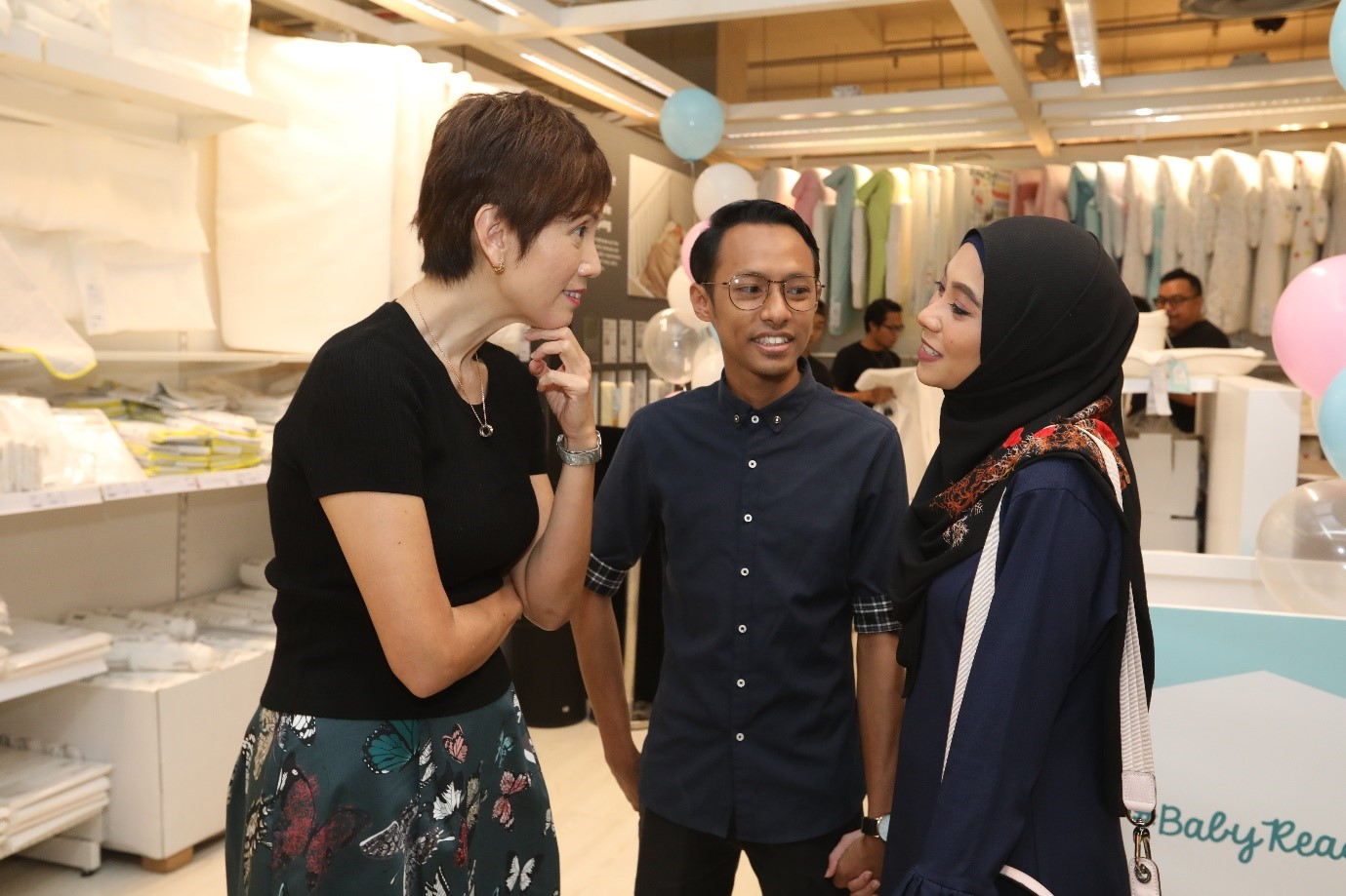 Minister Josephine Teo interacting with a couple who is currently expecting their first child (Muhammah Abdul Jabbar Bin Kassim, 27, senior technician Marianoor Binte Kam Sani, 21, customer service agent)