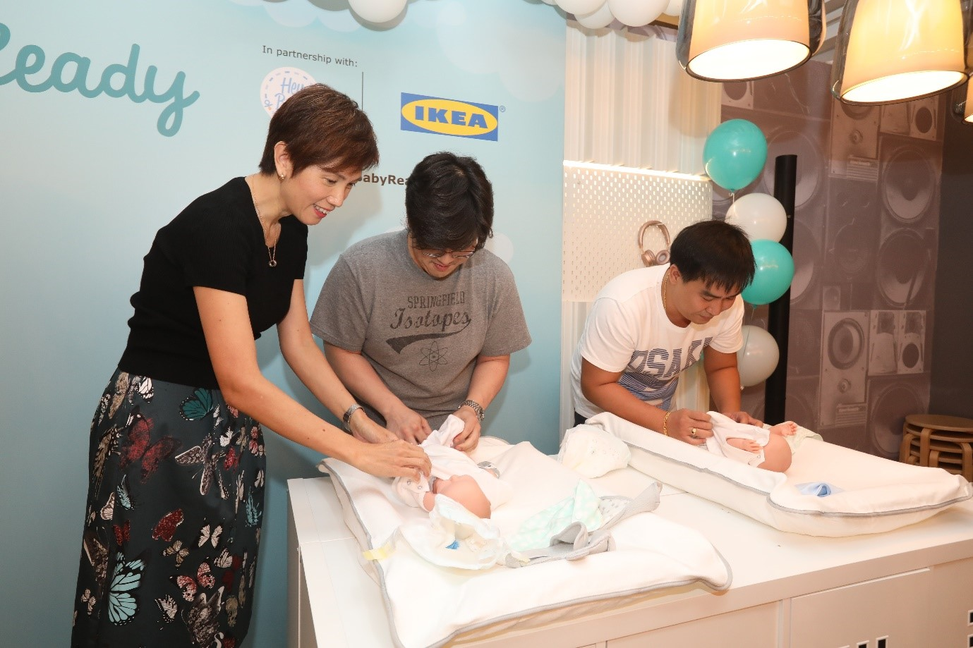 Minister Josephine Teo lending a hand to male contestants who are competing to be the fastest to clean and dress a baby mannequin. The activity encourages fathers to play a more active role in child caring.