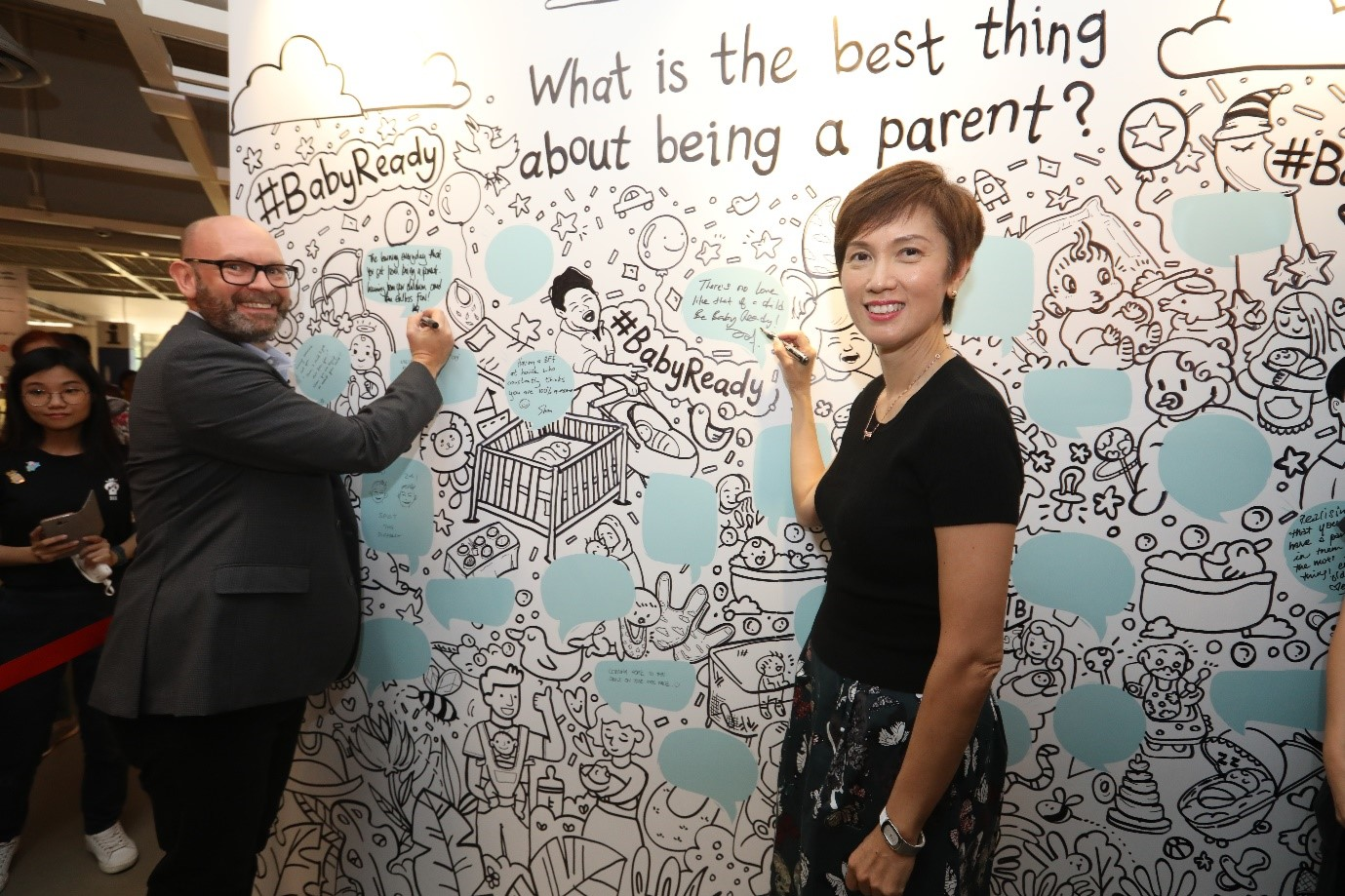 Minister Josephine Teo with IKEA Deputy Managing Director Mike King at the communal wall, where they penned their thoughts on the best thing about being a parent.