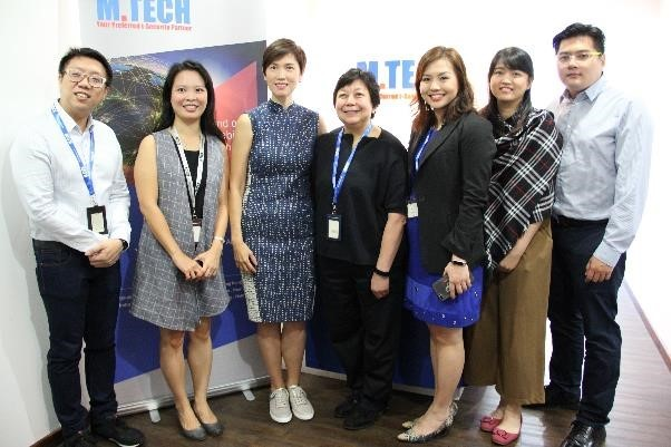 Minister Josephine Teo taking a group photo with M. Tech staff.